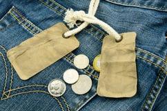 Blauer Baumwollstoff mit leerem Preis und Münzen auf Hintergrund Stockfotografie