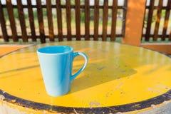 Blauer Becher auf gelber Tabelle, Vorderansicht der Kaffeetasse Lizenzfreies Stockfoto