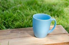 Blauer Becher auf hölzernem Brett mit grünem Gras Stockfoto