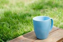 Blauer Becher auf hölzernem Brett mit grünem Gras Lizenzfreies Stockbild