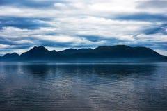 Blauer Berg über einem Fjord stockfotografie