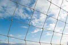 Blauer bewölkter Himmel durch Volleyballnetz stockfotos
