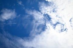Blauer bewölkter Himmel mit Passagierflugzeug Stockfoto