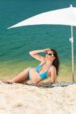 Blauer Bikini der Sommerstrand-Frau unter Sonnenschirm Lizenzfreies Stockfoto