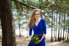 Blauer Blumenstrauß in den Händen des Mädchens in einem blauen langen Kleid Stockfoto