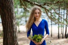 Blauer Blumenstrauß in den Händen des Mädchens in einem blauen langen Kleid Stockfotografie