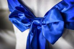Blauer Bogen und Schärpe auf Stuhl am Ereignis oder an der Aufnahme Lizenzfreie Stockfotos