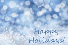 Blauer Bokeh-Weihnachtshintergrund, Schnee, simsen frohe Feiertage Stockfotografie