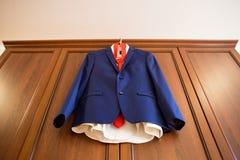 Blauer Br?utigamanzug mit der roten Bindung, die h?lzernes Kabinett h?ngt Der Morgen des Br?utigams stockfotos