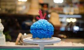 Blauer buttercream Kuchen mit rotem Anker vor Kuchenspeicher Stockfotos