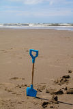 Blauer childs Spaten auf dem Strand mit Meer im Abstand Stockfotografie