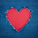Blauer Denimhintergrund mit rotem Herzen Stockfotografie