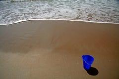 Blauer Eimer auf dem Strand Stockfotografie