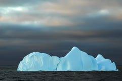 Blauer Eisberg mit dunklem Himmel Stockbild