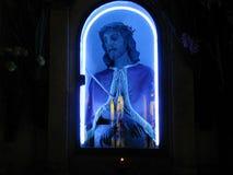 Blauer elektrischer Neonjesus im Glas schloss Schrein im Freien in Sizilien nachts ein Lizenzfreie Stockbilder