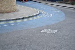 Blauer Fahrradweg auf einem scharfen schalten die Straße ein Lizenzfreies Stockfoto