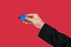 Blauer Flash-Speicher an Hand mit lokalisiertem rotem Hintergrund Stockbilder