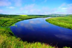 Blauer Fluss umgeben durch Wiese Stockfoto