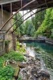 Blauer Fluss unter der Brücke Stockfotografie