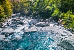 Blauer Gebirgsfluss und Sonne Stockfoto