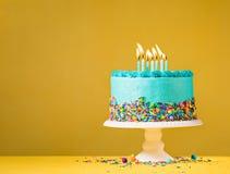 Blauer Geburtstags-Kuchen auf Gelb lizenzfreie stockbilder