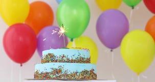Blauer Geburtstagskuchen mit Wunderkerze und bunten Ballonen stock video