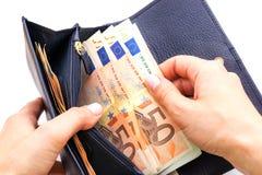 Blauer Geldbeutel mit Euros in den Händen auf weißem Hintergrund Lizenzfreie Stockfotografie