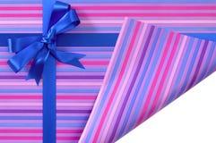 Blauer Geschenkbandbogen auf Süßigkeitsstreifenpackpapier, gefalteter offener aufschlussreicher weißer Kopieneckraum nach innen Stockfoto