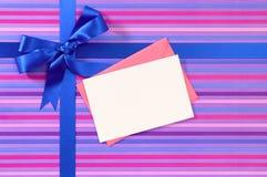 Blauer Geschenkbandbogen auf Süßigkeitsstreifenpackpapier, leerem Weihnachten oder Glückwunschkarte mit Umschlag Stockfotos