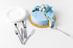 blauer geschmackvoller Kuchen auf hackendem Brett mit Kuchenserver und -platten Stockfoto
