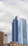 Blauer Glaskontrollturm, der von den älteren Gebäuden steigt Stockfoto
