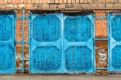 Blauer großer Garagentor gemacht von den Ziegelsteinen Stockfotografie