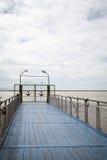 Blauer hölzerner Pier mit Geländer auf einem Fluss Geschlossene Tore verziert mit Ankern Lizenzfreies Stockfoto