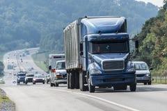 Blauer Halb-LKW mit anderem Verkehr auf Autobahn stockbild