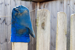 Blauer Handschuh getragen auf dem Zaun Lizenzfreie Stockfotos