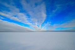 Blauer Himmel über einem schneebedeckten Feld stockbild