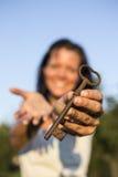 Blauer Himmel des Frauengoldschlüssels in der Hand Lizenzfreie Stockfotografie