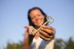 Blauer Himmel des Frauengoldschlüssels in der Hand Stockfotos