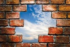 Blauer Himmel durch alte Backsteinmauer Stockfotografie