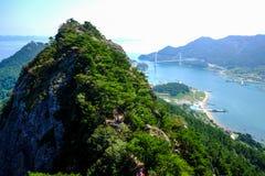 Blauer Himmel, felsige Bergspitze, Inseln und nebelhaftes Meer Lizenzfreie Stockbilder