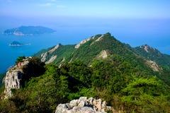 Blauer Himmel, Inseln, felsiger Berg und nebelhaftes Meer Stockbilder