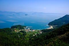 Blauer Himmel, Inseln, Küstendorf und nebelhaftes Meer Lizenzfreies Stockfoto