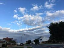 Blauer Himmel mit carpetted Wolken über Häusern stockfotos