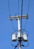 Blauer Himmel mit drei Transformatordrähten Stockbild