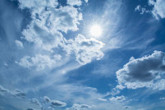 Blauer Himmel mit gelockten Wolken, Stockfoto