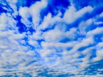 Blauer Himmel mit sich hin- und herbewegenden Federwolkewolken lizenzfreie stockfotos