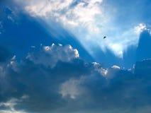 Blauer Himmel mit Sonne strahlt durch die Wolken aus Stockfoto