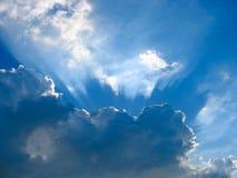 Blauer Himmel mit Sonne strahlt durch die Wolken aus Lizenzfreie Stockfotos