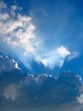 Blauer Himmel mit Sonne strahlt durch die Wolken aus Lizenzfreies Stockfoto
