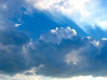Blauer Himmel mit Sonne strahlt durch die Wolken aus Stockbild